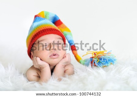 Close-up of sleeping newborn posed on white blanked, wearing colorful stocking cap - stock photo