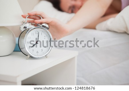 Close-up of sleepy woman in bed extending hand to alarm clock - stock photo