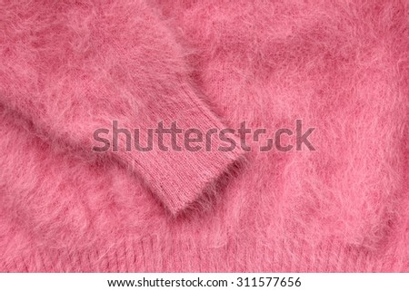 Close-up of sleeve of pink wool sweater. - stock photo