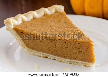 Close up of slice of homemade pumpkin pie sitting on white plate with fork and small pumpkin in background