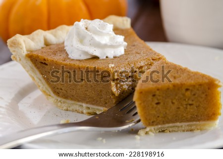 Close up of slice of homemade pumpkin pie sitting on white plate with whipped cream and fork cutting into pie