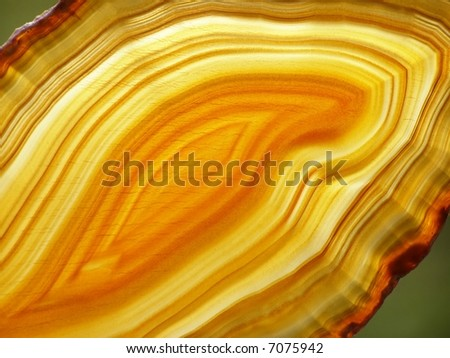 Close-up of slice of yellow agate against background