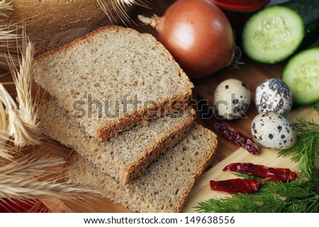 close-up of sliced bread on a cutting board and other edibles studio - stock photo