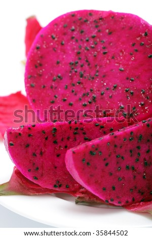 Close up of sliced red dragonfruits isolated over white background.