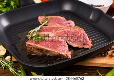 Close Up of Slices of Rare Roast Beef Frying on Ridged Skillet Cast Iron Pan and Seasoned with Fresh Herbs of Rosemary - stock photo