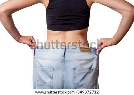 Close-up of slim waist of young woman in big jeans showing successful weight loss, isolated on white background, diet concept.