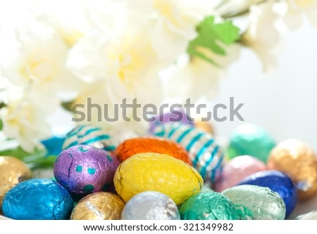 Close up of small chocolate Easter eggs in the basket. - stock photo