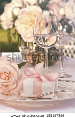 Close-up of small gift on plate at wedding reception - stock photo