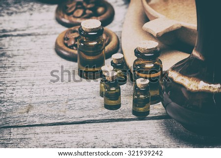 Close-up of small glass vials filled with natural aromatic essential oils next to crock, bamboo utensils with water and coffee beans on old wooden planks. Toned image in retro style. Copy space - stock photo