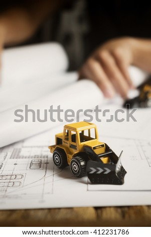 Close up of small replica of an excavator or truck on blueprint architectural project. Vintage tone. - stock photo