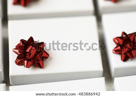 Close up of small white gift boxes with red bows.