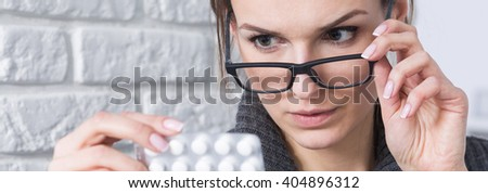 Close-up of smart young woman in glasses checking drug's composition before using - stock photo