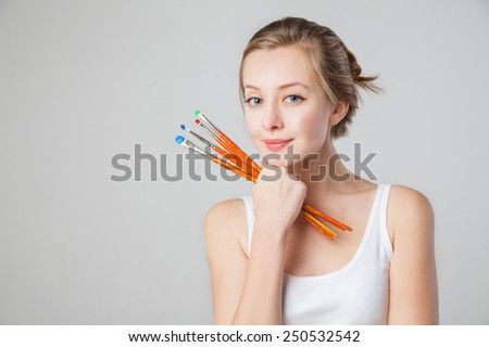 Close-up of smiling artist-girl with paintbrush. Isolated. - stock photo