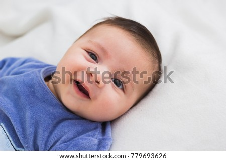 close up of smiling baby lying in his crib