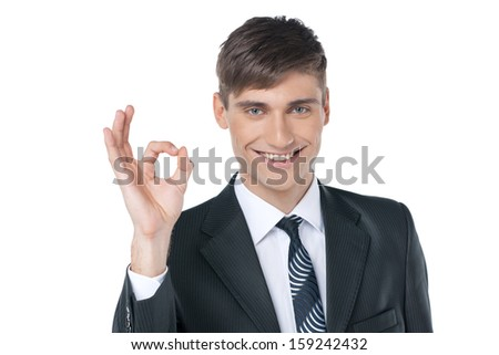 Close up of smiling businessman showing an OK gesture. Standing isolated on white