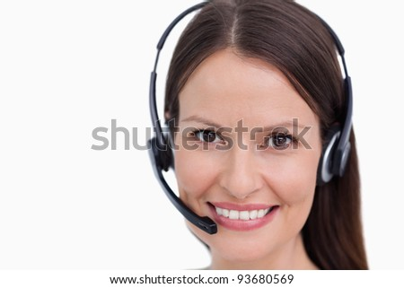 Close up of smiling female call center employee against a white background