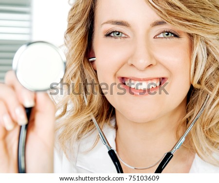 Close-up of smiling female doctor holding stethoscope, looking at camera - stock photo