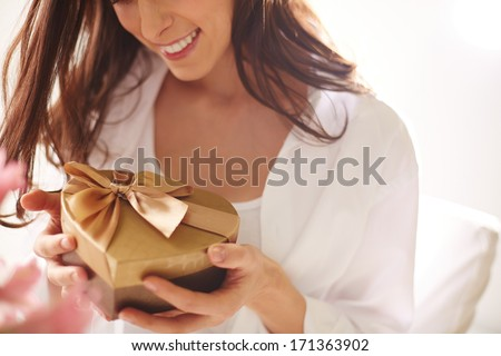 Close-up of smiling female holding heart shaped giftbox - stock photo
