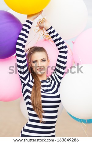 close-up of smiling girl with smokey eye make up, ponytail hair in short black and white striped dress keeps her hands raised holding bunch of multicolored balloons - stock photo