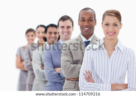 Close-up of smiling people dressed in suits crossing their arms in a single line with focus on the first woman
