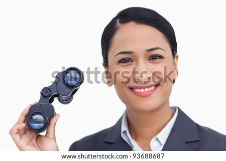 Close up of smiling saleswoman with spy glasses against a white background - stock photo