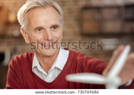 Close up of smiling senior man touching wind turbine