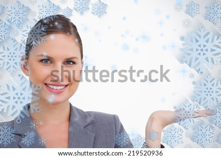 Close up of smiling tradeswoman holding her palm up against snowflake frame