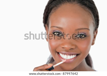 Close up of smiling woman applying lip gloss against a white background - stock photo