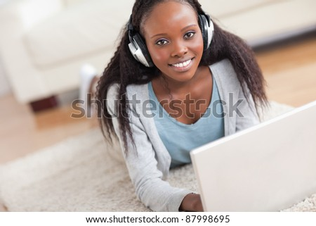 Close up of smiling woman lying on the floor with her laptop enjoying music
