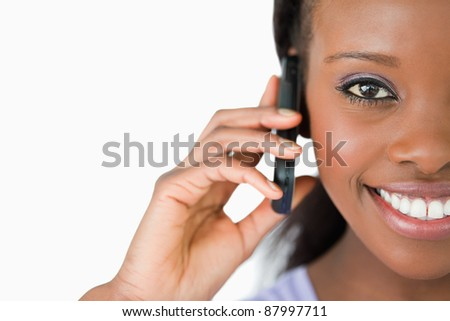 Close up of smiling woman on her phone against a white background - stock photo