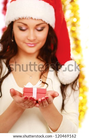 Close-up of smiling woman with gift isolated on christmas decorated background - stock photo