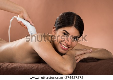 Close-up Of Smiling Young Woman Lying On Front Receiving Epilation Laser Treatment - stock photo