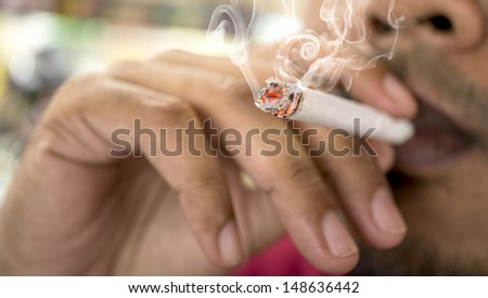 Close-up of Smoking cigarette - stock photo