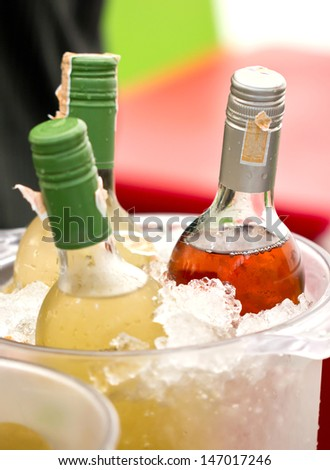 Close up of soft drink bottles in ice bucket. - stock photo