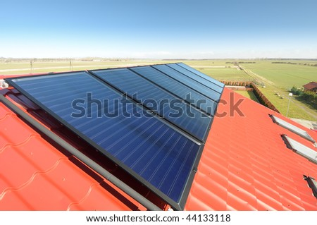 Close up of solar panels on red tiled roof and beautiful blue sky. - stock photo