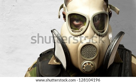 Close-up Of Soldier Wearing Mask against a concrete background - stock photo