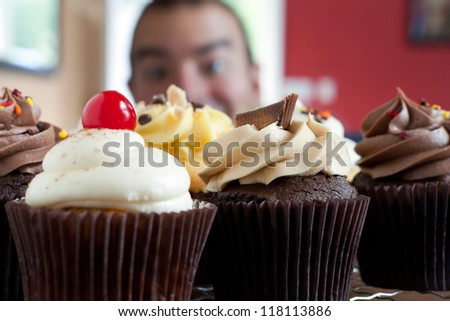 Close up of some decadent gourmet cupcakes frosted with a variety of frosting flavors.  Shallow depth of field with the face of a hungry man lurking in the background.