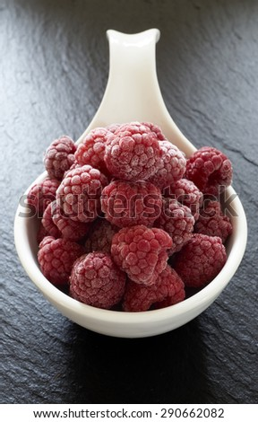 Close up of some frozen raspberries in a white porcelain dish on a slate platter - stock photo