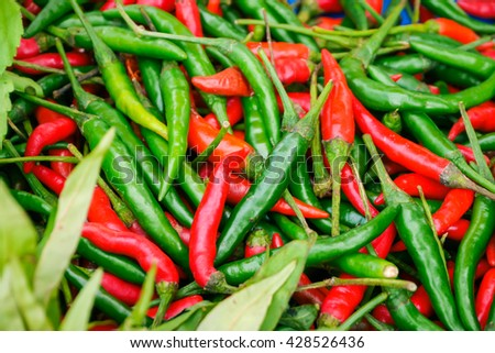 Close-up of some red and green chillies mixed up for sale in a market - stock photo