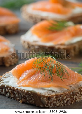 Close-up of some wheat sandwiches with smoked salmon on a wooden table