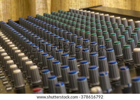 Close-up of sound mixer controller with knobs and sliders - stock photo