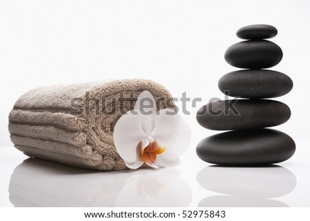 close up of spa treatment luxury treatment with hot stones and orchid - stock photo