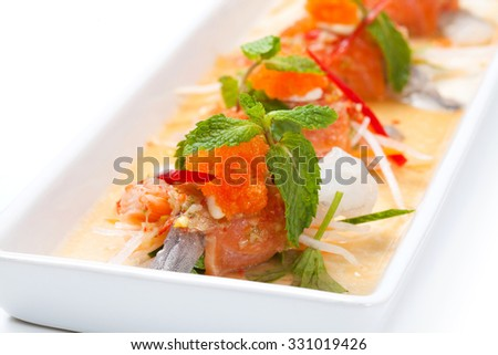 close up of spicy salmon with mixed raw prawn and crab stick on white plate