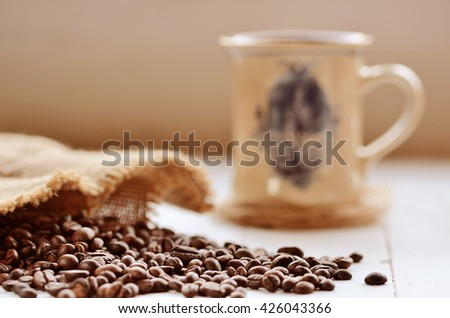Close-up of spilled coffee beans from canvas sack and ceramic mug in background - stock photo
