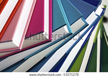 Close-up of spiral stack of multi-colored real books. - stock photo