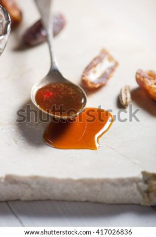 Close up of spoonful of sweet date syrup and few dates. - stock photo