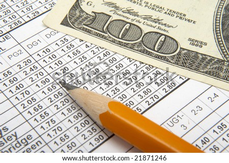 close up of sports betting slip, pencil and one hundred dollars - stock photo