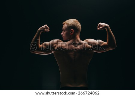 Close up of sports man's muscular back isolated on black background - stock photo