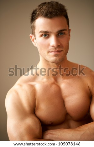 Close up of sporty man with muscular arms crossed on brown background - stock photo