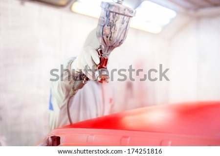 Close-up of spray gun and worker painting a car - stock photo